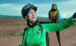 Em Campo Limpo de Goiás, arara pega carona em ciclista durante trilha (Foto: Sirlene Bessa Guimarães/Arquivo)